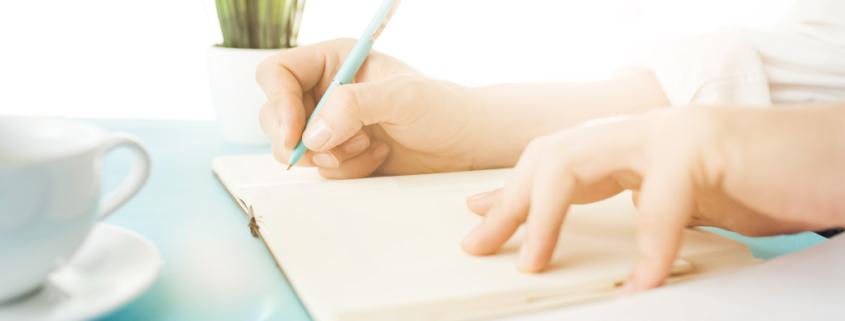 """Jemand schreibt mit dem Stift in ein Notizbuch, man sieht nur die Hände auf dem Tisch, Titelbild """"Befolge keine Schreibtipps"""", besser bloggen, regelmäßig schreiben, produktiv bloggen"""