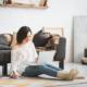 Frau sitzt im Wohnzimmer auf dem Fußboden und schreibt am Laptop. Täglich bloggen, Fokus auf Bloggen, 28 Tage Content, Blogparade