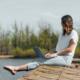 Eine Frau sitzt auf einem Steg am Wasser und schreibt auf einem Laptop, erfolgreich bloggen, entspannt und zielgerichtet bloggen, Spaß am Schreiben