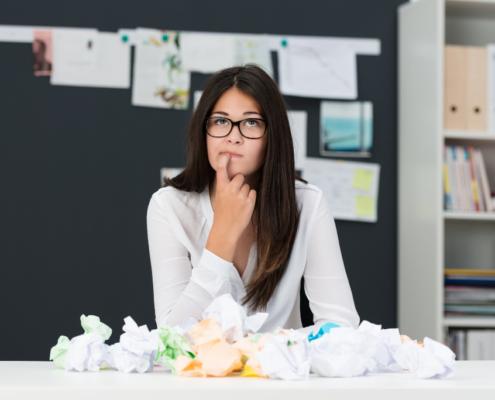 Junge Frau am Schreibtisch denkt nach, grübelt. Zerknülltes Papier liegt vor ihr. Wie wichtig ist der erste Satz beim Bloggen? Lesbarkeit beim Bloggen, Textverständlichkeit