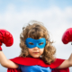 Siegerpose: Ein junges Mädchen im Superheldinnenkostüm mit Boxhandschuhen reckt seine Hände in die Höhe. Leser erreichen, besser texten, Texte schreiben, Kunden überzeugen, Leser überzeugen