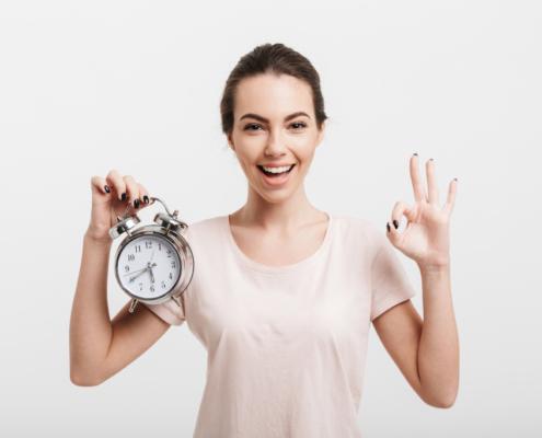 """Eine Frau hält einen Wecker in der Hand und macht mit der anderen das Zeichen für """"ausgezeichnet"""", Symbolbild: Blogartikel schneller schreiben Titel"""